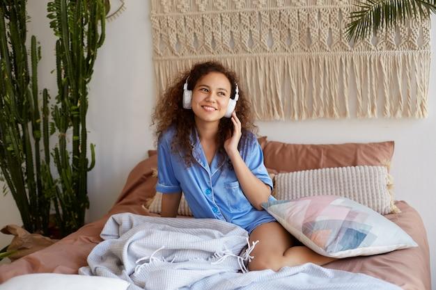 Allegra giovane ragazza mulatta riccia vestita in pigiama blu, sdraiata a letto, sorridente e godersi la sua canzone preferita in cuffia, distoglie lo sguardo e sembra felice.