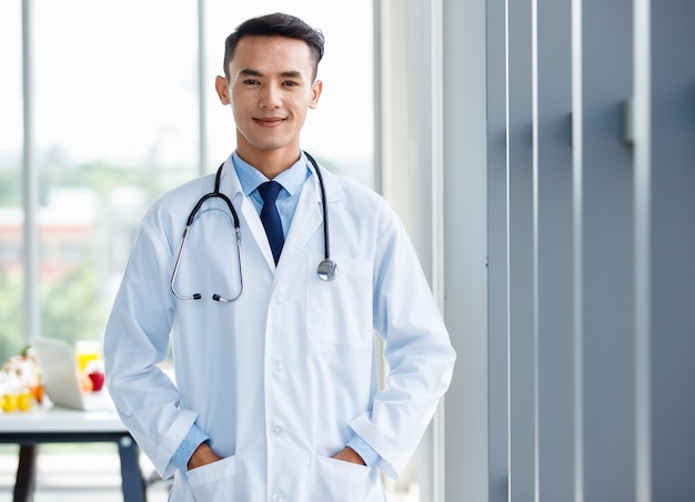 Cheerful young  and cute asian male doctor in uniform and with stethoscope standing in clinic and pose with positive and self confident gesture.