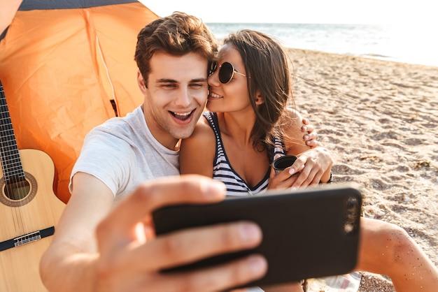 Веселая молодая милая влюбленная пара делает селфи по мобильному телефону на пляже на открытом воздухе