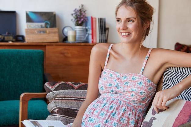 Веселая молодая милая беременная женщина отдыхает дома, выглядит позитивно, о чем-то мечтает, живот распух, ждет малыша.