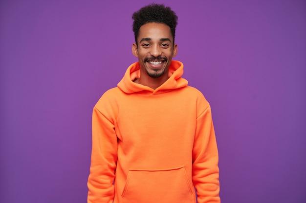 明るい若い黒髪のひげを生やしたブルネットの男性、暗い肌は手を下に紫の上に立っている間、気持ちよく笑って、気分が良い