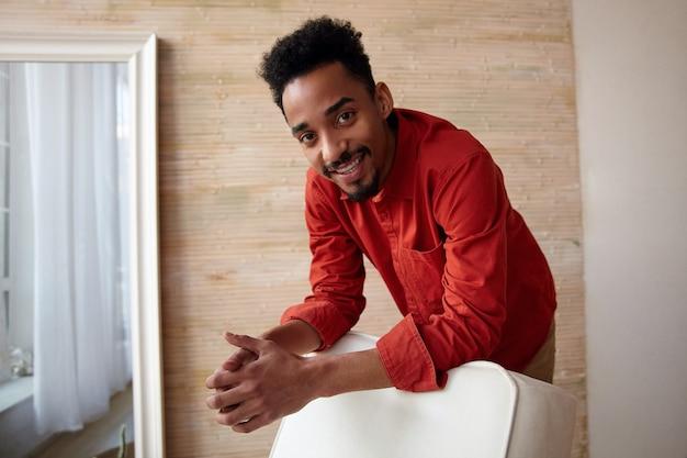 Веселый молодой темнокожий брюнет с бородой, одетый в повседневную одежду, радостно смотрит с широкой улыбкой, позируя в домашнем интерьере