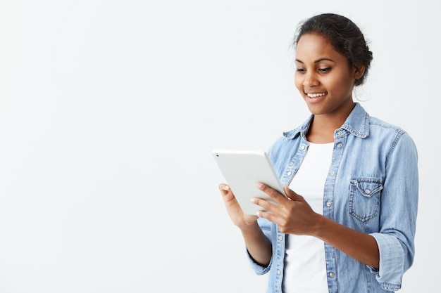Giovane studentessa dalla pelle scura allegra con il sorriso sveglio che sta sulla parete bianca, facendo uso della compressa, controllando il newsfeed sui suoi account del social network. ragazza afroamericana graziosa che pratica il surfing internet sulla t