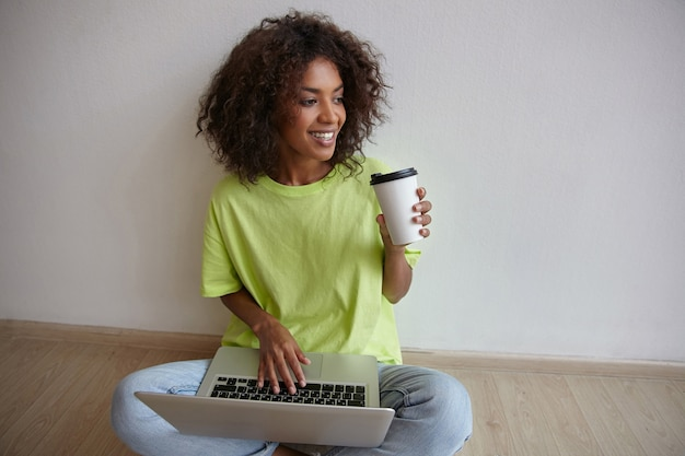 Cheerful young dark skinned female in yellow t-shirt and blue jeans sitting on floor with laptop and drinking coffee, working remotely from home