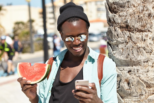 Cheerful young dark-skinned male spending nice time outdoors