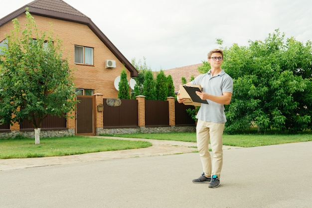 Cheerful young delivery man in eyeglasses holding a cardboard box, smiling and looking, standing near the private house, outdoors.
