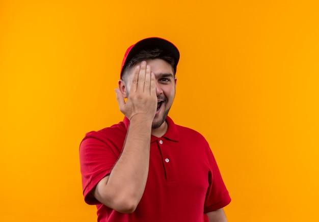 赤い制服を着た陽気な若い配達人と大きく笑っている手で片目を閉じるキャップ