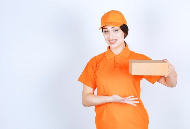 白い壁に手でパッケージを保持している陽気な若い配達女性