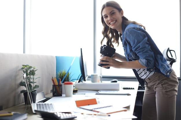 Веселый молодой дизайнер с помощью цифровой камеры, стоя возле стола в своем творческом офисе.
