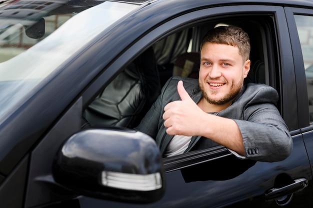 Веселый молодой водитель смотрит в камеру