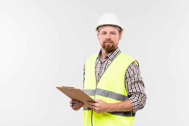 Веселый молодой инженер с буфером обмена, глядя на вас, стоя перед камерой в изоляции