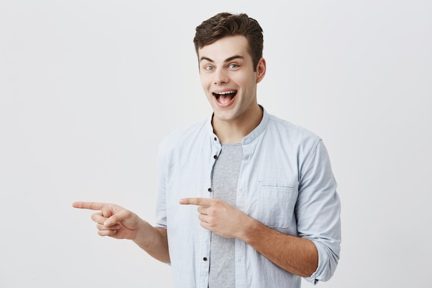 Cheerful young european male with dark hair and blue eyes, winking, dressed in blue shirt pointing forefingers away indicating copy space on white blank wall for content or promotional information