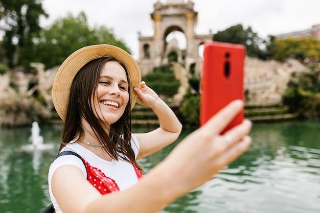スマートフォンで自分撮りの肖像画をしながら楽しんでいる陽気な若いヨーロッパの女性