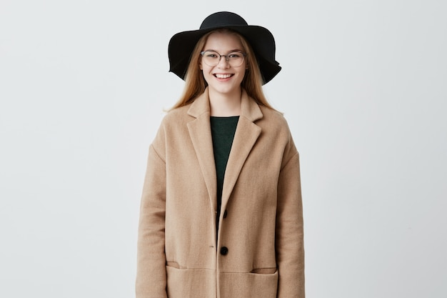 Cheerful young european woman with beautiful set of features, dressed in coat over green sweater, wearing her blonde hair loose, with eyeglasses on, looking  with charming smile