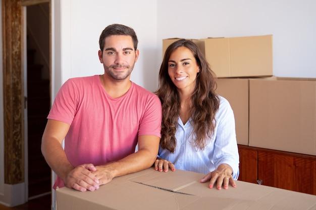 Allegro coppia giovane famiglia in movimento nella nuova casa, in piedi alla scatola di cartone,