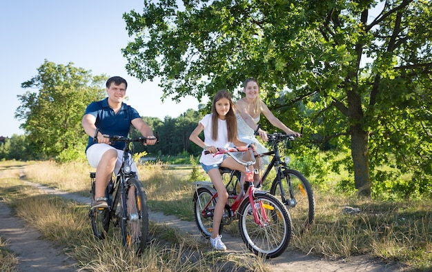 Cheerful young family cycling in meadow at hot sunny day