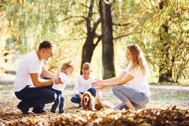 Cheerful young family have a rest in an autumn park together.