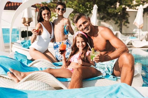 Веселая молодая семья веселится в бассейне