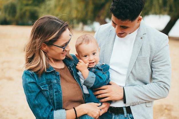 赤ちゃんを抱いて彼に微笑んでいる陽気な若い家族