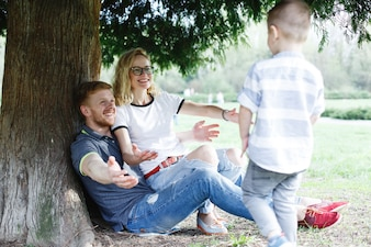 Cheerful young family of mom, dad and little son have fun playing under the green tree