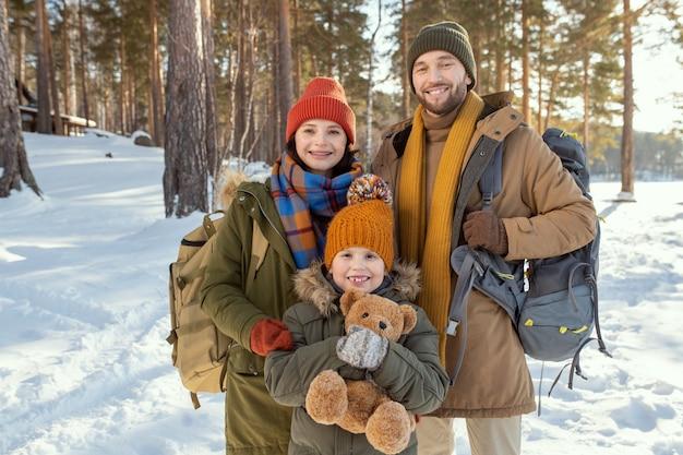 自然環境に対してカメラの前に立って、外であなたを見ている暖かい冬の服を着た3人の陽気な若い家族