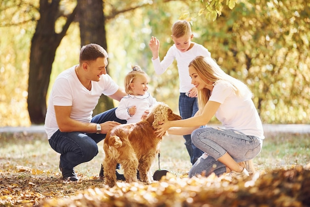 Cheerful young family with dog have a rest in an autumn park together.