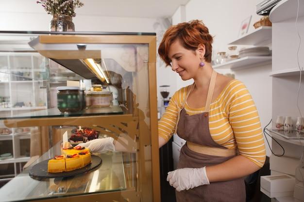 Веселая молодая женщина-кондитер устраивает показ в своем кафе