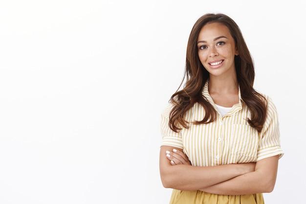쾌활한 젊은 여성 교차 팔 자신감 포즈, 즐겁게 웃고, 흰 벽 위에 서서 고객 질문에 기꺼이 대답하고, 즐거운 캐주얼 대화를 하고, 편안하고 열정적입니다.