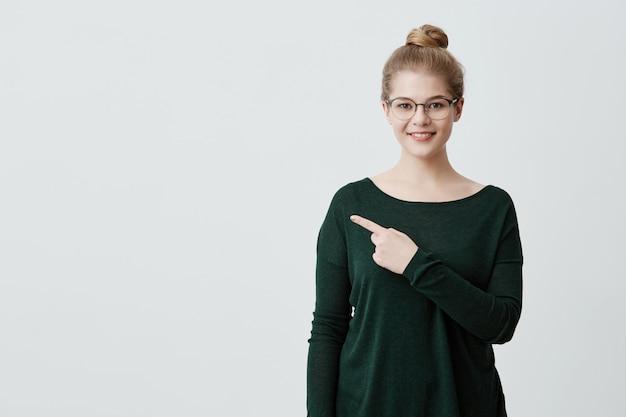 陽気な若い女性客またはカジュアルな緑のセーターと眼鏡笑顔で金髪の学生とテキストまたは広告情報の灰色のcopyspace壁に人差し指を指している笑顔