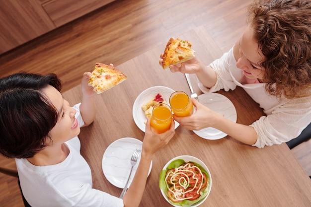 Веселые молодые подруги едят пиццу и пьют сок на ужин дома, вид сверху