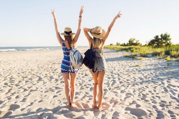 해질녘 해변에서 함께 걷는 쾌활 한 젊은 여자 친구