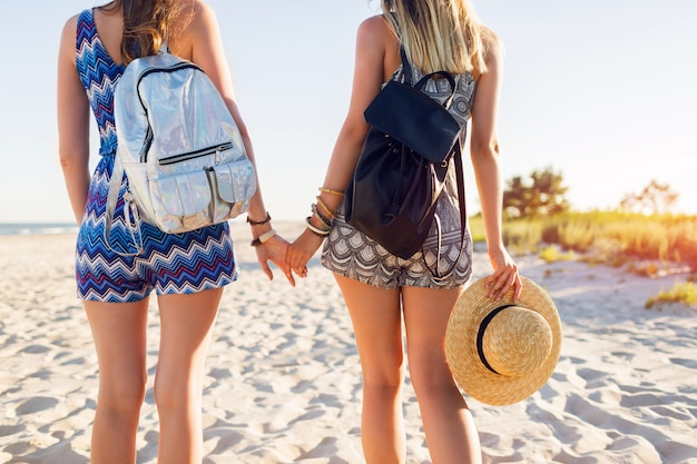Веселые молодые подруги гуляют вместе на пляже на закате