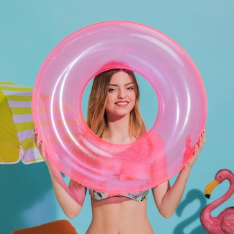 Cheerful young female holding floating circle in studio