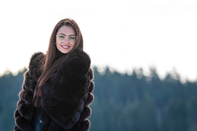 Веселая молодая женщина в теплой шубе, наслаждаясь зимним днем в снежном лесу