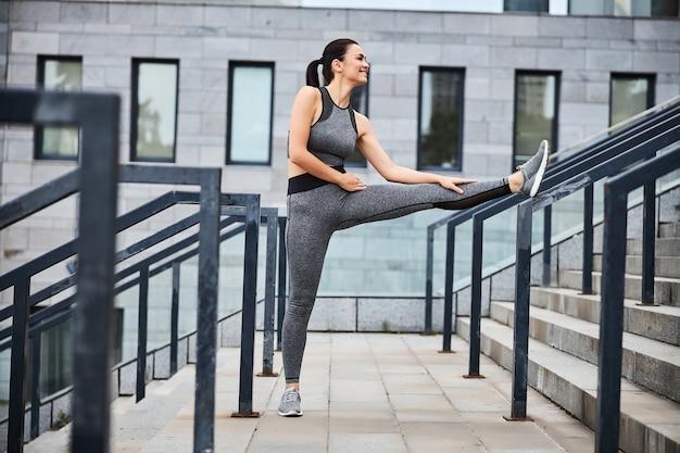 쾌활한 젊은 여성은 도시 건물의 계단에서 훈련 후 다리 유연성을 운동하고 있습니다