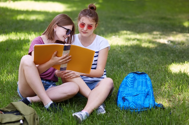 Cheerful young female laughs gladfully while reads something funny in book, sits near her best female friend