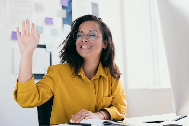 쾌활한 젊은 여성 회사원이 누군가를 맞이하기 위해 그녀의 손을 올렸습니다.