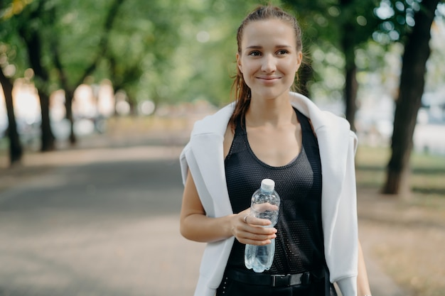 쾌활한 젊은 여성 주자가 물병을 들고 활동적인 옷을 입고 야외에서 포즈를 취합니다.