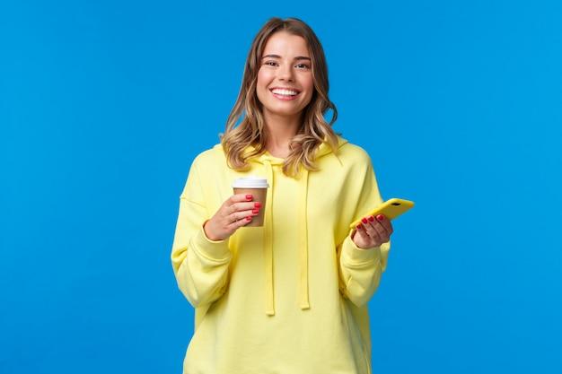 쾌활 한 젊은 여성 학생 카페 주문 테이크 아웃 커피 근처에 서, 종이 컵에서 마시는 휴대 전화를 들고, 하얀 미소를 빛나는, 카메라를보고 만족