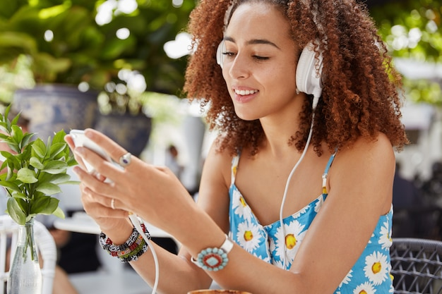 Cheerful young female with dark skin and afro hairstyle listens music in playlist on smart phone via headphones, downloads audiobook via mobile application