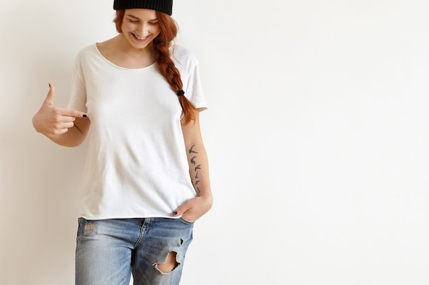 Cheerful young female with ginger hair and tattoo looking down and pointing index finger at her white oversize t-shirt