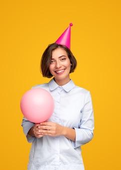 분홍색 풍선 웃고 노란색 배경에 생일을 축하하는 동안 카메라를보고 쾌활한 젊은 여성