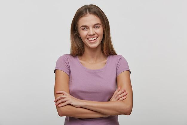 快い笑顔で陽気な若い女性、長い茶色の髪、健康な肌、カジュアルなtシャツを着て、手を組んで立っています。