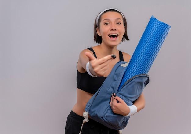 Giovane ragazza allegra di forma fisica nello zaino di hlding degli abiti sportivi con la fabbricazione felice e positiva della stuoia di yoga viene nel gesto che sta sopra il muro bianco