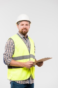 Cheerful young foreman or engineer with clipboard looking at you while standing in front of camera