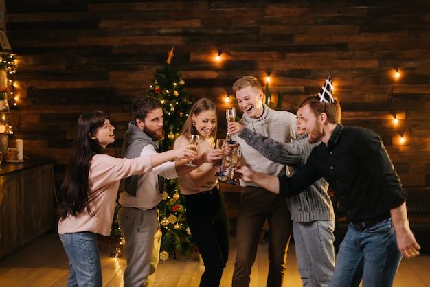 陽気な若い友達がシャンパングラスでチリンと鳴り、新年を祝っています。背景に花輪とお祝いのイルミネーションとクリスマスツリー。友達はクリスマスイブを祝っています。