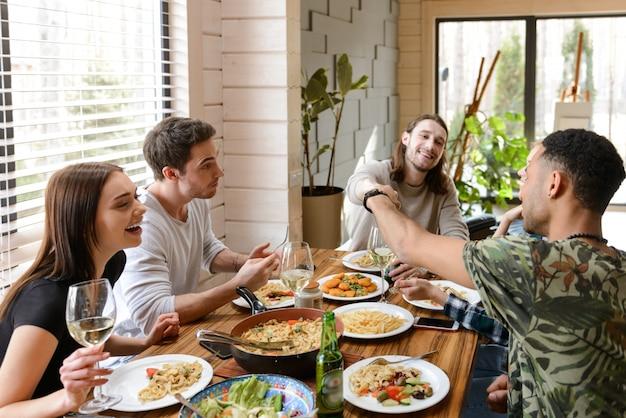 Веселые молодые друзья едят и веселятся за столом