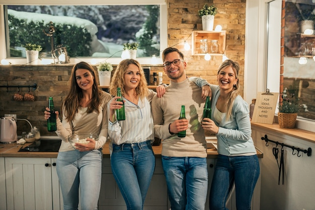 Cheerful young friends standing in cozy apartment with bottles of beer, looking at camera.