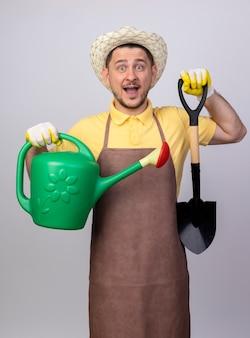 じょうろと幸せそうな顔で笑顔のシャベルを保持している作業用手袋でジャンプスーツと帽子を身に着けている陽気な若い庭師の男