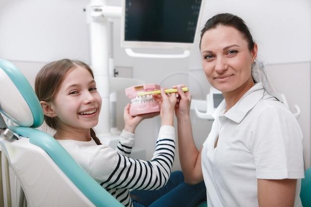 Веселая молодая девушка и ее стоматолог, улыбаясь в камеру